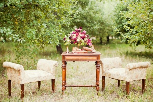 A seating area outside at a wedding reception decorated with vintage furniture.