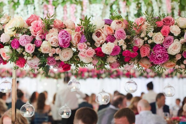 A wedding reception decorated with a hanging floral installation of pink flowers.