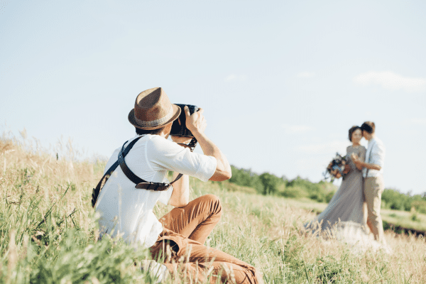 A photographer taking a picture of a bride and groom standing in a field.