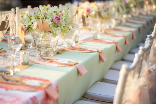 A table set with mint green table cloths and pink napkins.